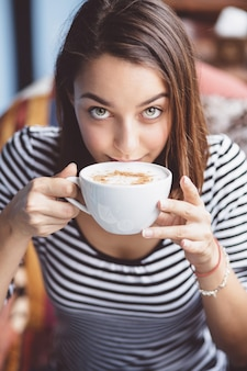 Mujer joven bebiendo café en café urbano