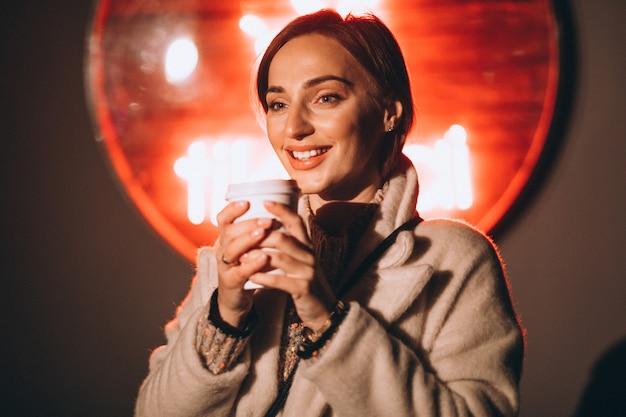 Mujer joven bebiendo café en la calle de noche