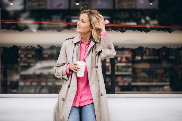 Mujer joven bebiendo café en la ciudad