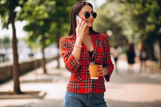 Mujer joven bebiendo café y hablando por teléfono