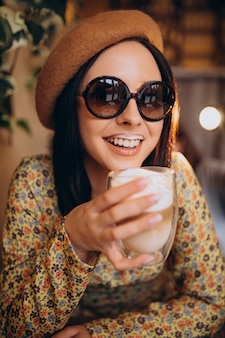 Mujer joven bebiendo café con leche en un café