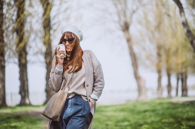 Mujer joven bebiendo café en el parque
