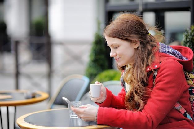 Mujer joven bebiendo café y usando su teléfono inteligente en un café parisino de la calle