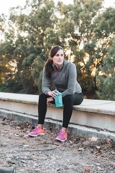 Mujer joven bebiendo para hacer deporte
