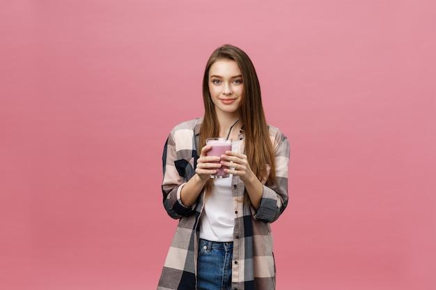 Mujer joven bebiendo jugo batido con paja