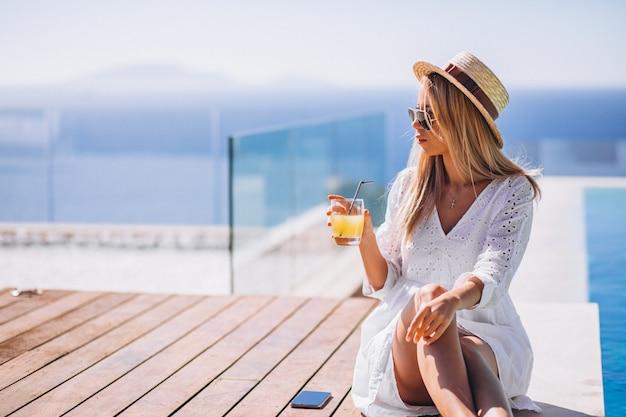 Mujer joven bebiendo jugo bu la piscina