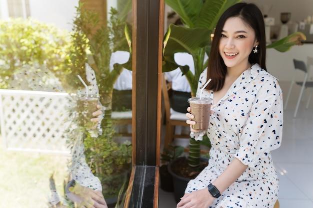 Mujer joven bebiendo leche con chocolate helada en un café