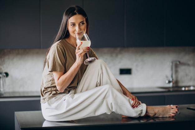 Mujer joven bebiendo limonada de vidrio en la cocina