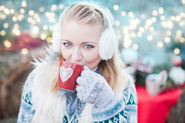 Mujer joven bebiendo ponche en mercado de navidad.