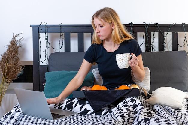 Mujer joven bebiendo una taza de café o té y leer las noticias en la computadora portátil después de despertarse por la mañana en casa