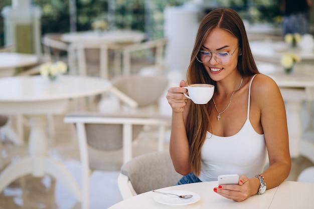 Mujer joven bebiendo té y usando el teléfono