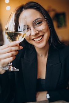 Mujer joven bebiendo vino blanco en un restaurante