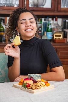 Mujer joven bebiendo vino y comiendo queso solo en la sala de estar. mujer comiendo bocadillos de queso y bebiendo vino para relajarse después del trabajo.