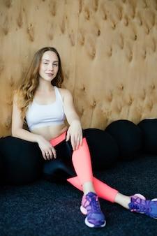 Mujer joven belleza fitness después de entrenar en la colchoneta de deporte