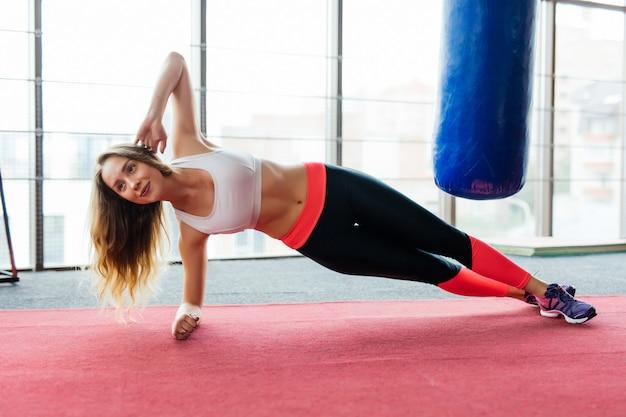 Mujer joven belleza fitness de pie en la plancha en el gimnasio en el interior