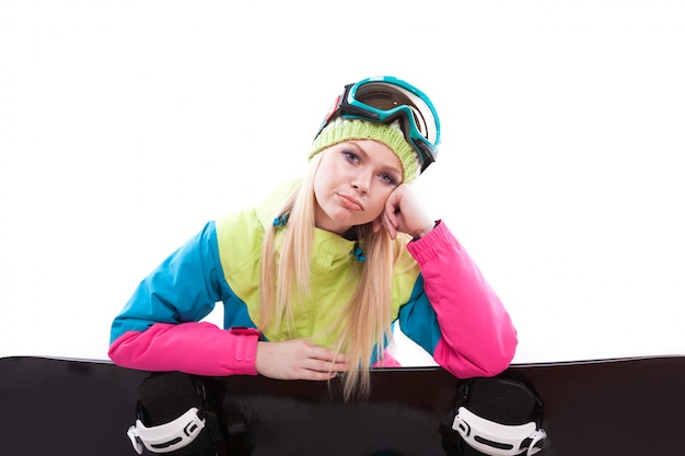 Mujer joven belleza en traje de esquí y gafas de esquí sentarse con sbowboard