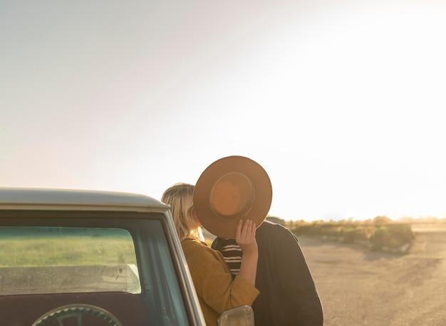 Mujer joven besando a su pareja detrás del sombrero
