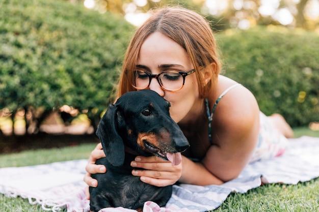 Mujer joven besando a su perro lindo