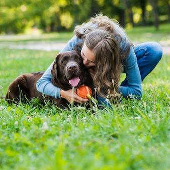 Mujer joven, besar, ella, perro, en el estacionamiento