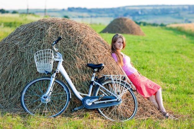 Mujer joven con una bicicleta en campo con pajares