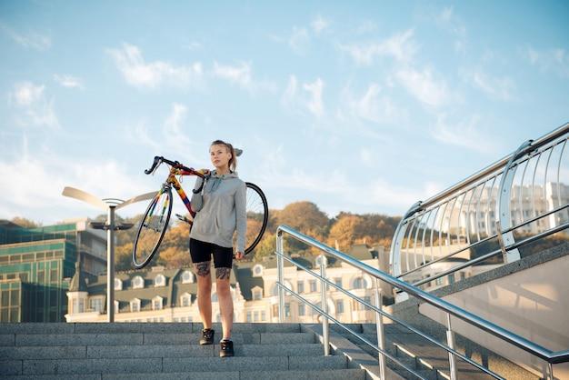 Mujer joven y bicicleta en la ciudad