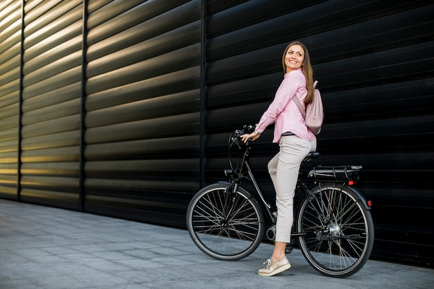 Mujer joven con bicicleta eléctrica moderna de la ciudad como transporte urbano sostenible limpio