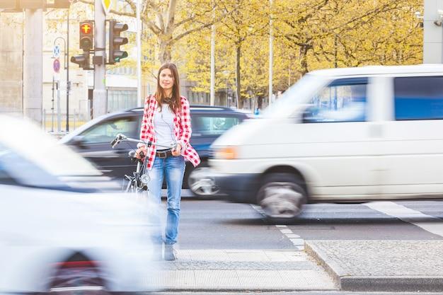Mujer joven con bicicleta esperando para cruzar la calle.