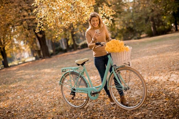 Mujer joven con bicicleta con smartphone en el parque otoño