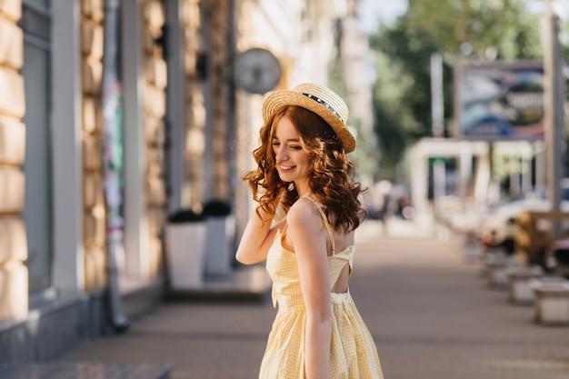 Mujer joven bien formada en vestido amarillo posando con placer en la ciudad. foto al aire libre de la impresionante chica con sombrero disfrutando de la sesión de fotos durante la caminata.