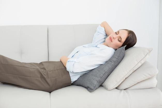 Mujer joven bien vestida durmiendo en el sofá