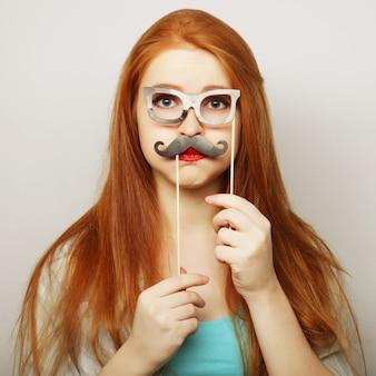 Mujer joven con bigotes falsos.