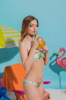 Mujer joven en bikini con bebida