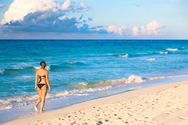 Mujer joven en bikini caminando por playa exótica