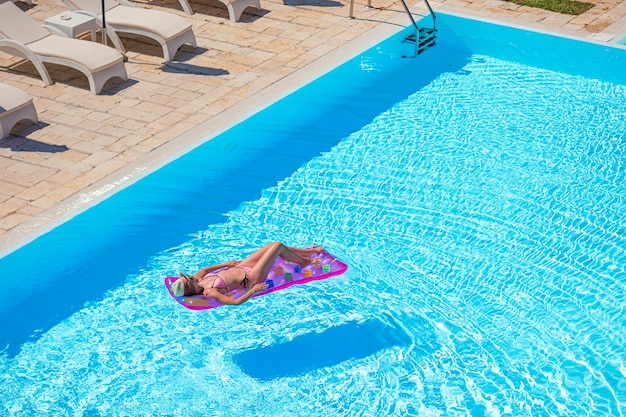 Mujer joven en bikini colchón de aire en la gran piscina