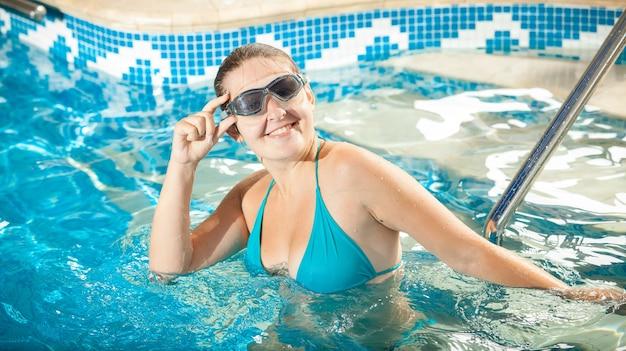 Mujer joven en bikini y gafas sonriendo a la cámara en la piscina