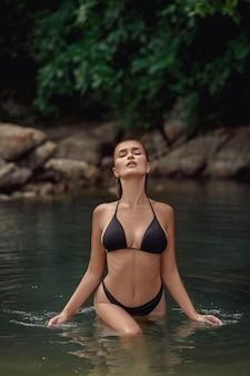 Mujer joven en bikini negro de pie en el agua después de nadar con los ojos cerrados. disfrutando de las vacaciones de verano
