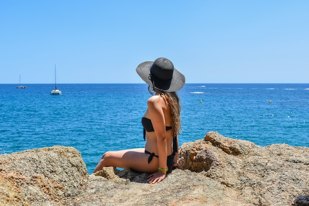 Mujer joven en bikini negro con sombrero posando en las rocas rodeadas por el mar