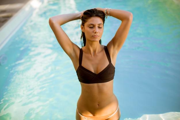 Mujer joven en bikini posando junto a la piscina al aire libre