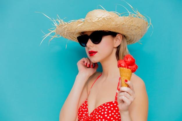 Mujer joven en bikini rojo y sombrero de paja con helado