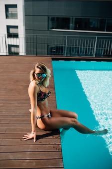 Mujer joven en bikini sentada en el borde de la piscina, al aire libre