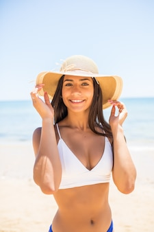 Mujer joven en bikini con sombrero de paja blanco disfrutando de las vacaciones de verano en la playa. retrato de hermosa mujer latina relajante en la playa con gafas de sol.