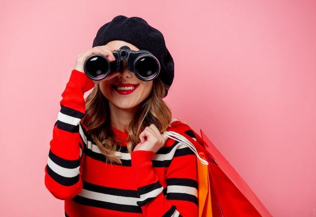 Mujer joven con binoculares y bolsas de compras en pared rosa