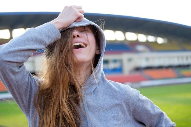 Mujer joven blanca pelirroja en gris con capucha relajante en el campo de fútbol y sonriendo.
