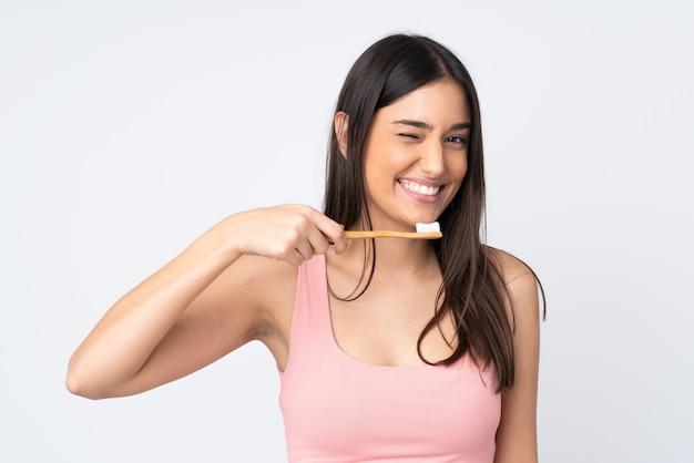 Mujer joven en blanco con un cepillo de dientes