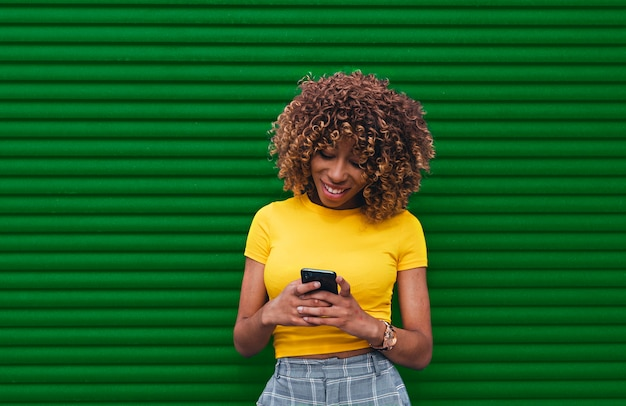 Mujer joven en una blusa amarilla sosteniendo el teléfono con ambas manos