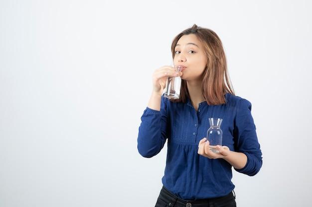 Mujer joven en blusa azul bebiendo un vaso de agua.