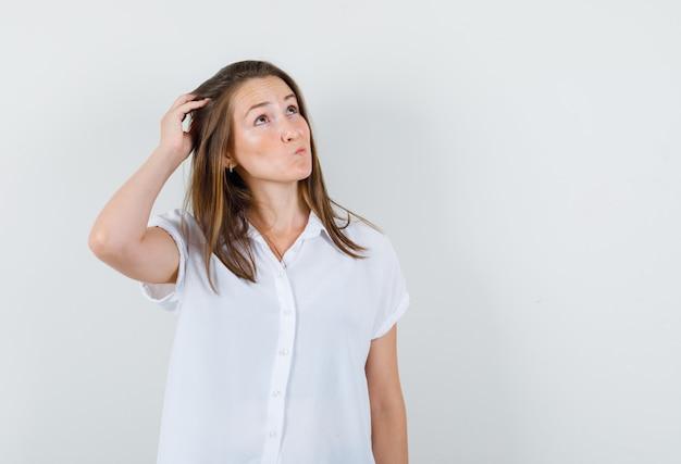 Mujer joven en blusa blanca mirando hacia arriba mientras sostiene la mano en la cabeza y mirando perplejo