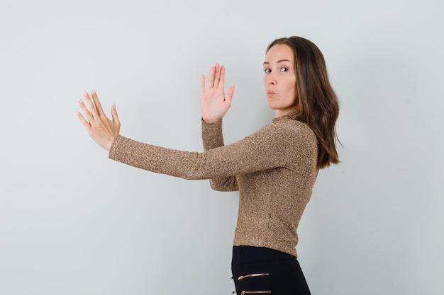 Mujer joven en blusa dorada mostrando chuleta de karate y mirando enfocado.