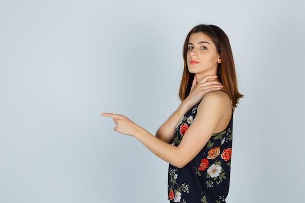 Mujer joven en blusa con la mano en el cuello, apuntando hacia adelante y mirando confiado.
