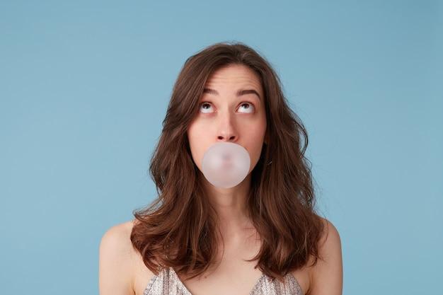 Mujer joven en blusa plateada con chicle